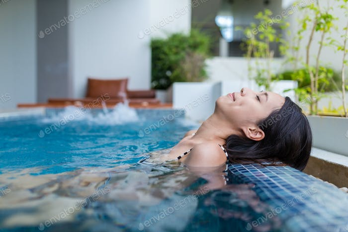Young Woman relaxing in jacuzzi pool