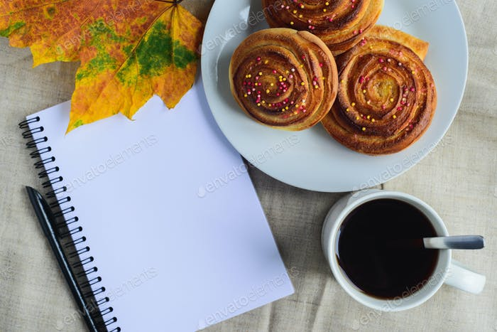 cinnamon buns with topping on plate, cup of coffee, open notepad and pen, autumn leaf on table