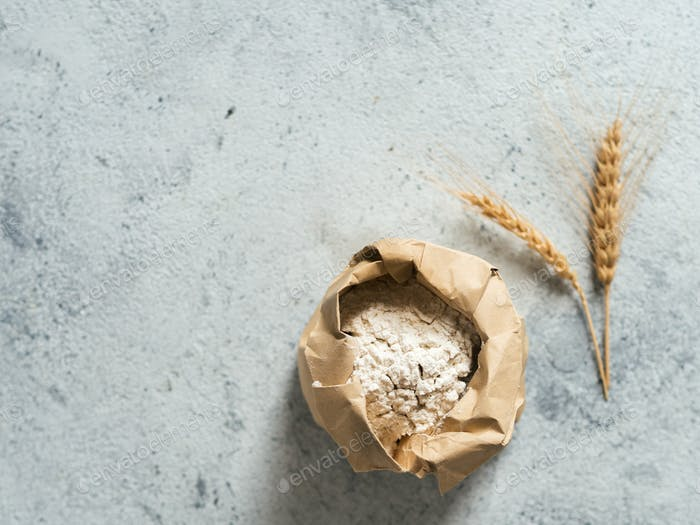 Wheat flour in paper bag on gray cement background