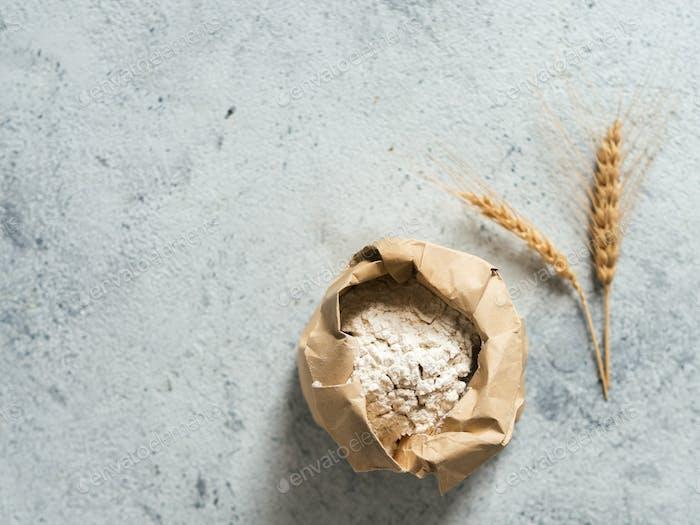 Weizenmehl in Papiertüte auf grauem Zementhintergrund