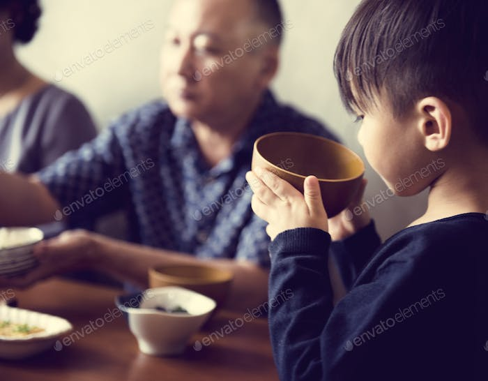 Japanese boy holding a bowl of soup