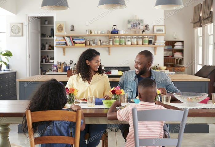 Black family of four having lunch in their kitchen at home