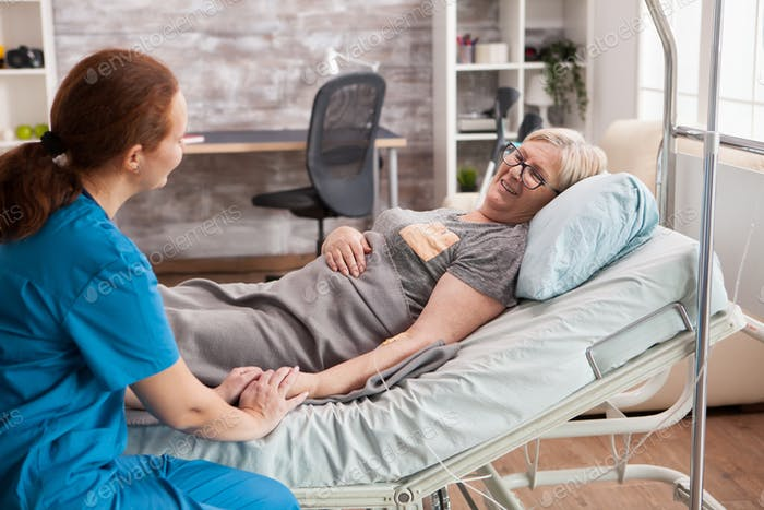 Female doctor in nursing home holding hand of old woman