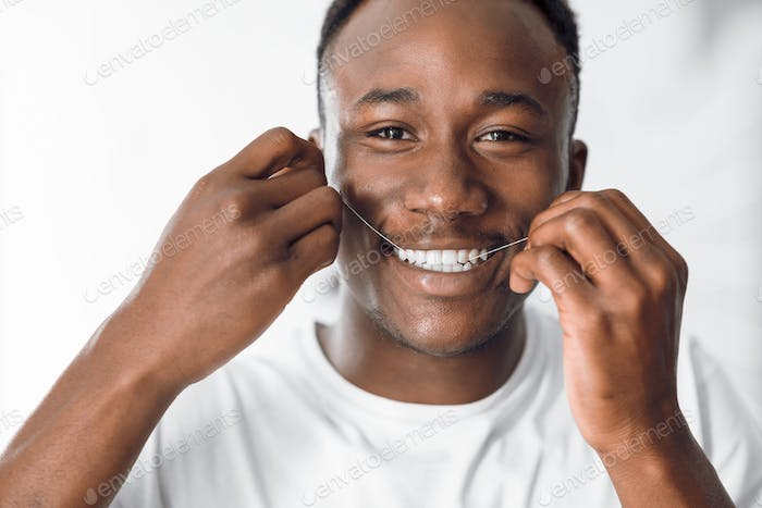 Happy Black Man Flossing Teeth Using Dental Floss In Bathroom