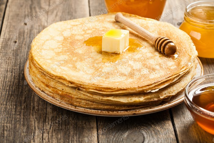 Homemade pancakes and various honey on wooden table