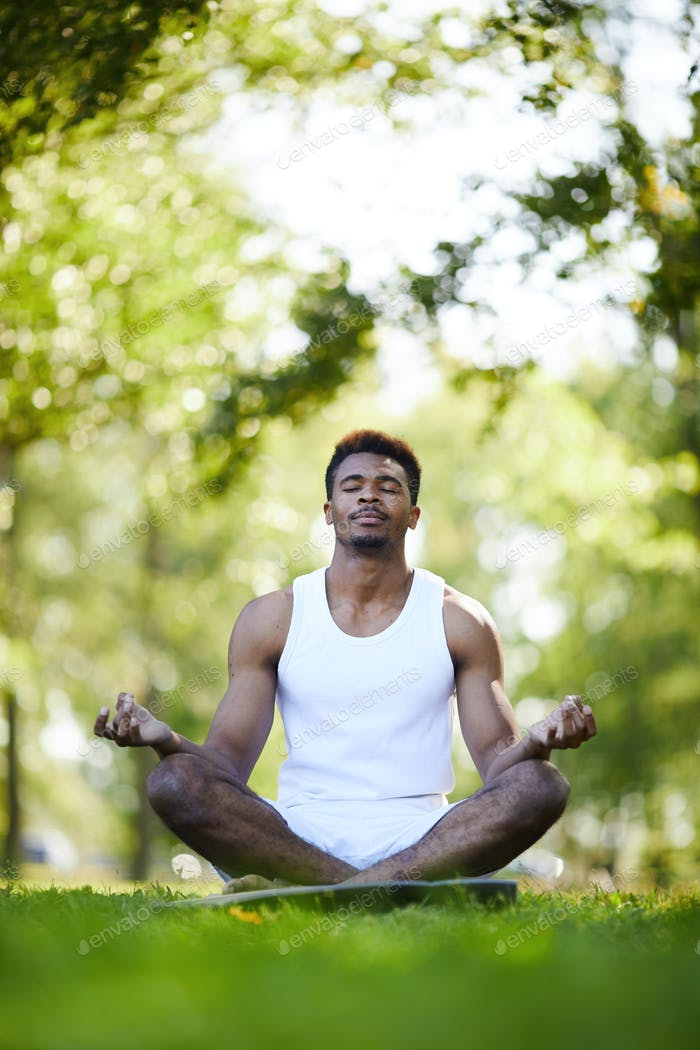 Serious black man with crossed legs meditating in park