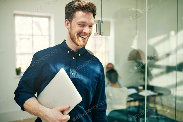 Laughing young businessman walking with his laptop at work