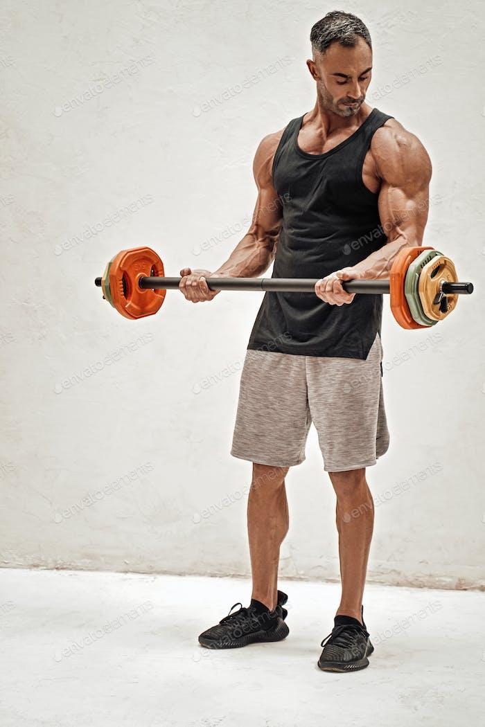 Fitness-Trainer posiert auf dem weißen Betonhintergrund Blick auf seine Pumpen Bizeps