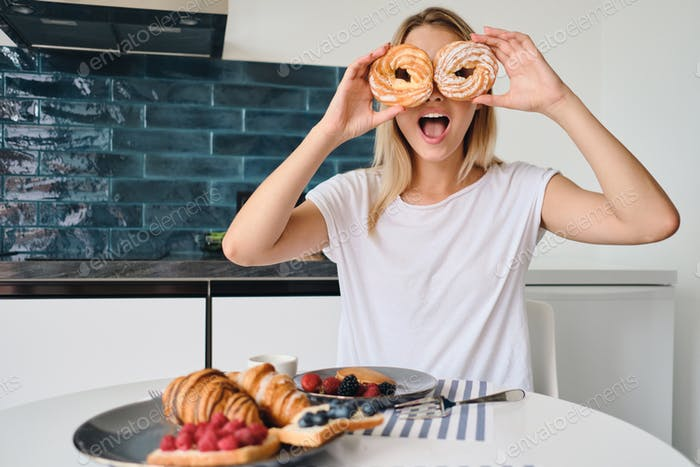 Young attractive blond woman covering eyes with sweet buns amazedly looking in camera