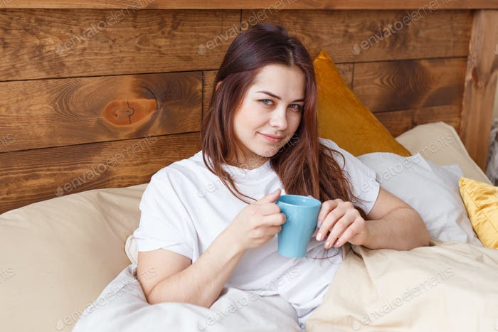 Half asleep young woman drinking coffee on bed.