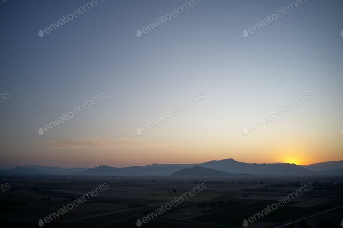 Aerial view of mountain valley at sunset.