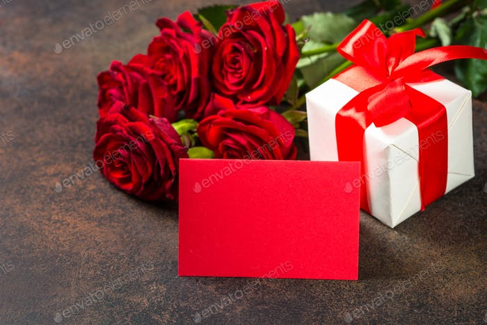 Holiday background with card, present and flowers.