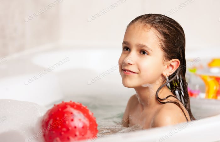 Cute cheerful little caucasian girl bathes and plays the ball and rubber ring