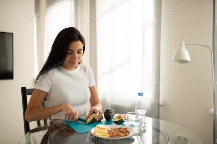 Positive female cutting avocado making snack