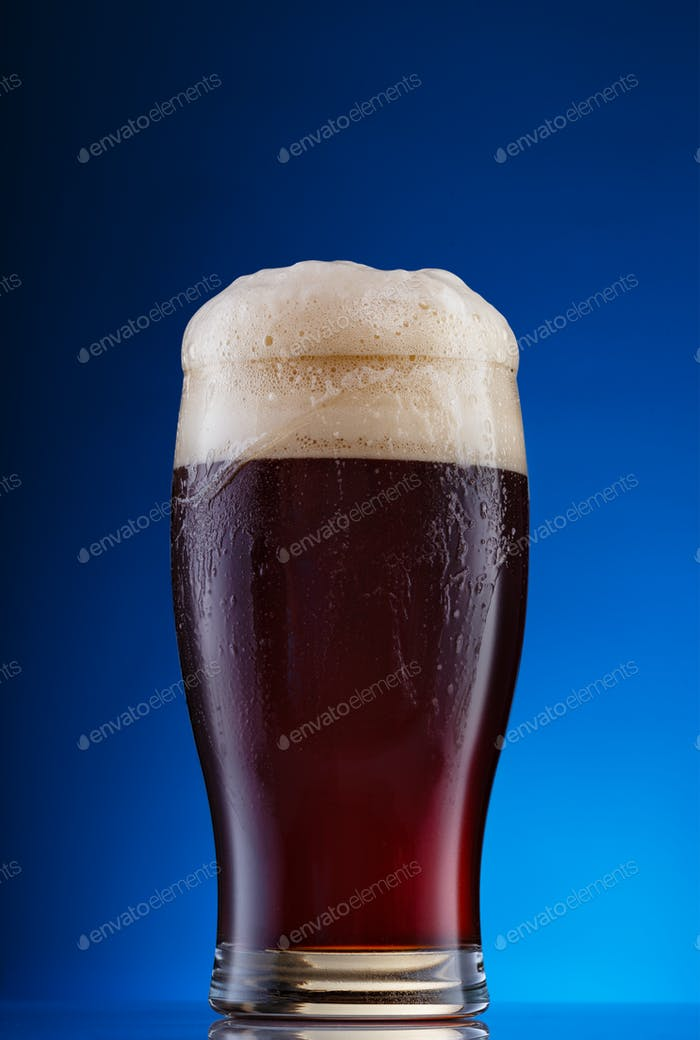 Glass of dark beer with foam on blue background
