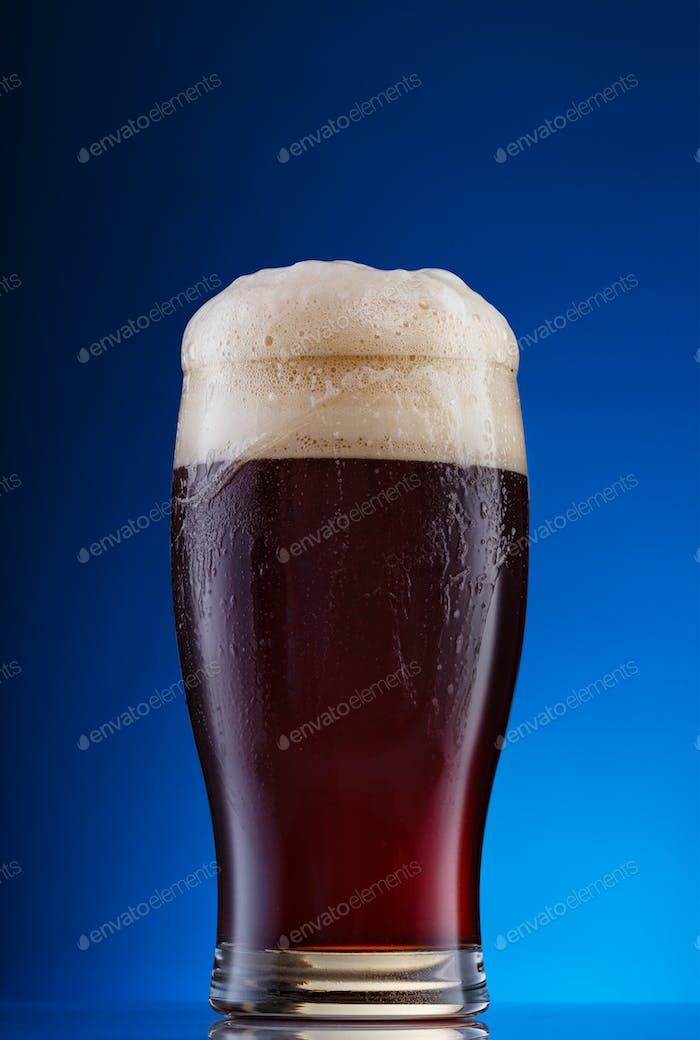 Glas dunkles Bier mit Schaum auf blauem Hintergrund
