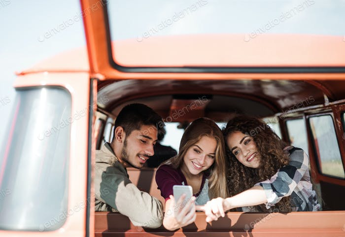 A group of young friends on a roadtrip through countryside, taking selfie.