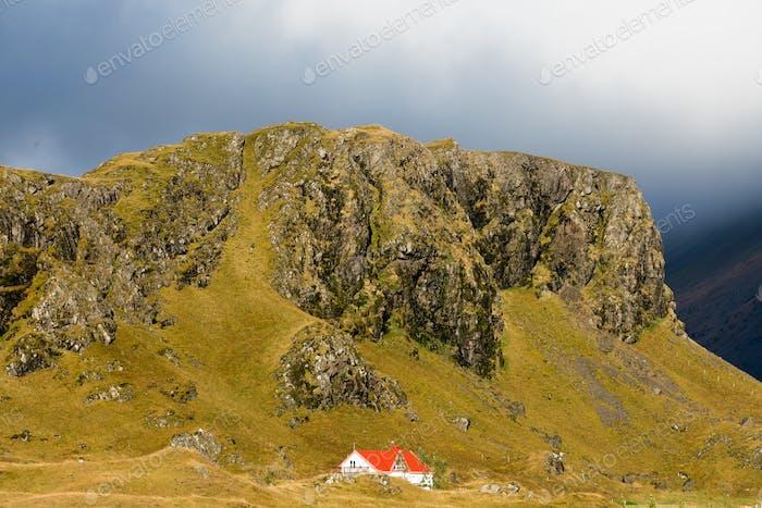 Bauernhaus am Fuße der Felsenklippe East Island