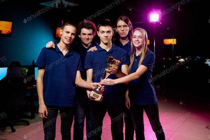 Five cheerful and successful e-sports competition winners holding golden statue