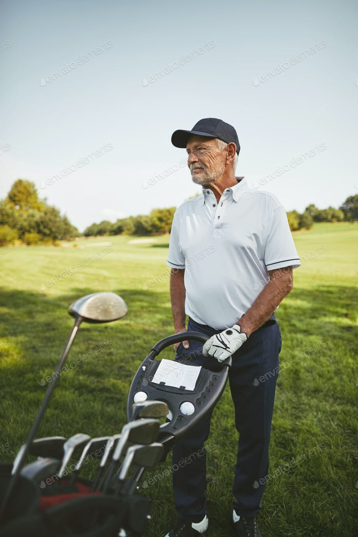 Senior man standing with his golf clubs on a fairway