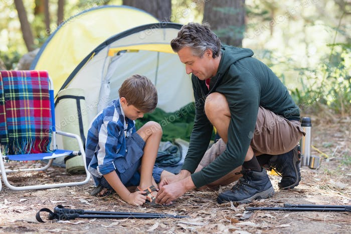 Father helping son to wear sandals by tent
