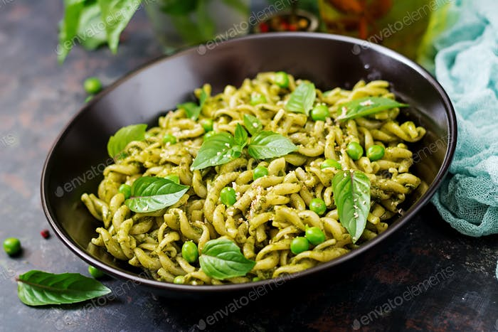 Fusilli pasta with  pesto sauce, green peas and basil. Italian food.
