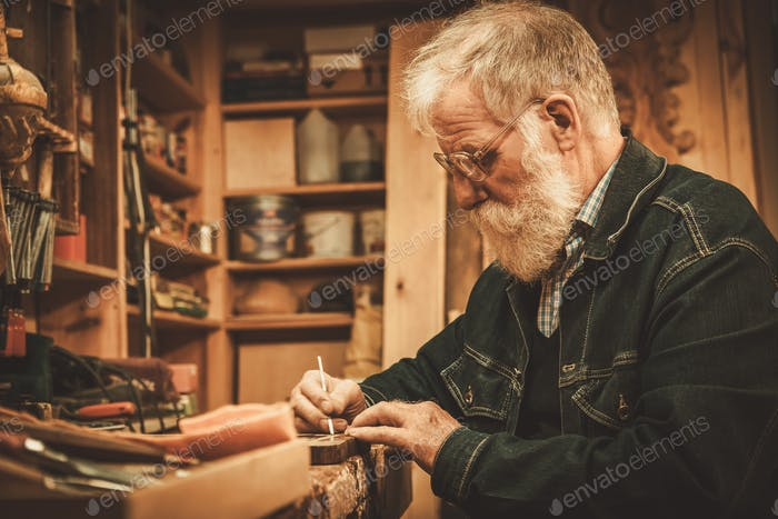 Senior restorer working with antique decor element in his workshop