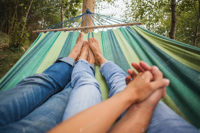 man and woman in love lying in hammock embracing, holding hands together, legs close-up