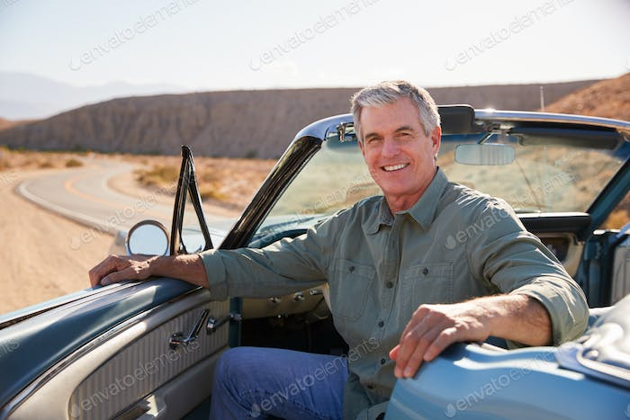 Senior man smiling to camera from parked open top car