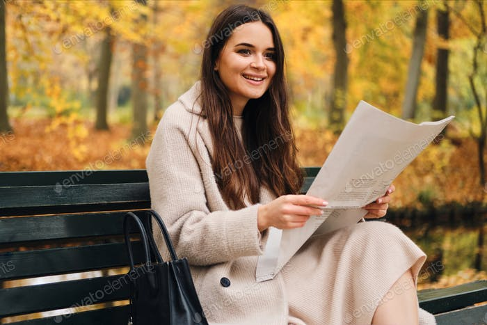 Pretty smiling brunette girl happily reading newspaper on bench in autumn park
