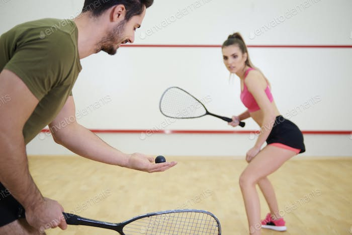 Athletic couple playing squash together