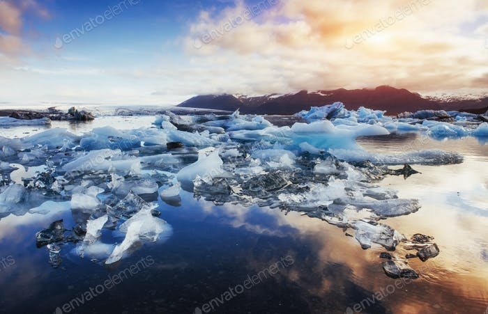 Icebergs in the glacial lake with a mountain