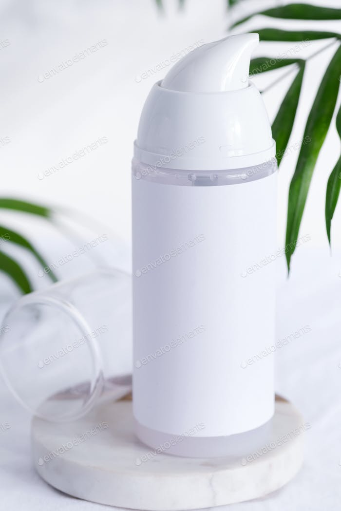 White shaving foam or cleaning lotion bottle mock up on a marble table with evergreen palm leaves