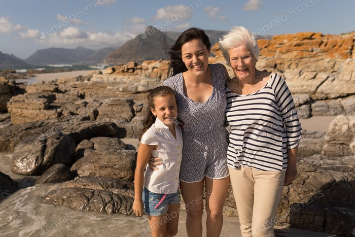 Front view of happy multi-generation family looking at camera on beach in the sunshine