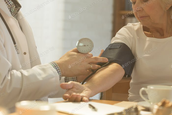 Doctor checking woman's blood pressure