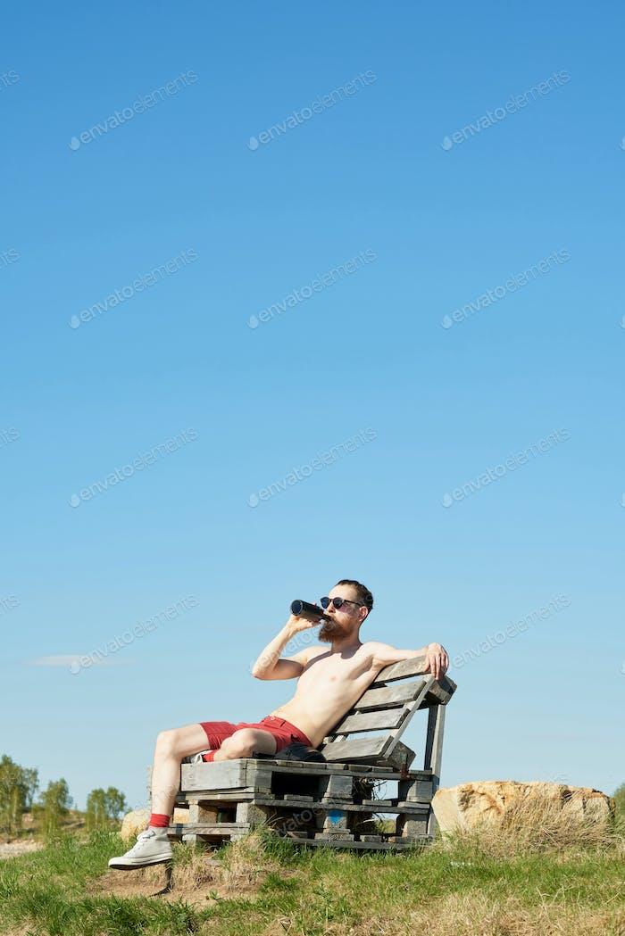 Man Enjoying Beer On Summer Day
