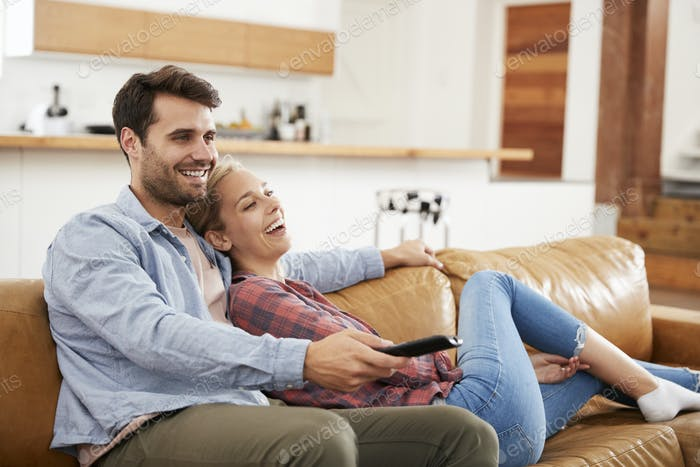 Couple Sitting On Sofa Watching Television Together