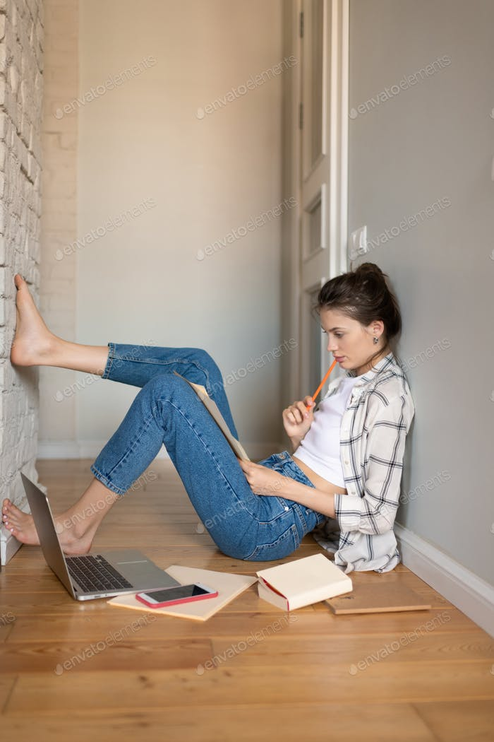 Teenage girl reading notes sitting on floor