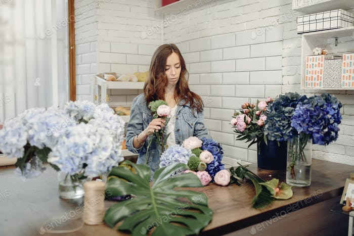 Florist in a flower shop making a bouquet