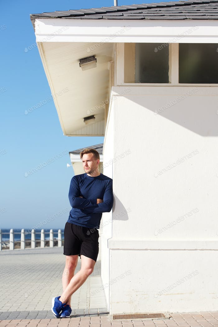 confident young sports man leaning on wall outside
