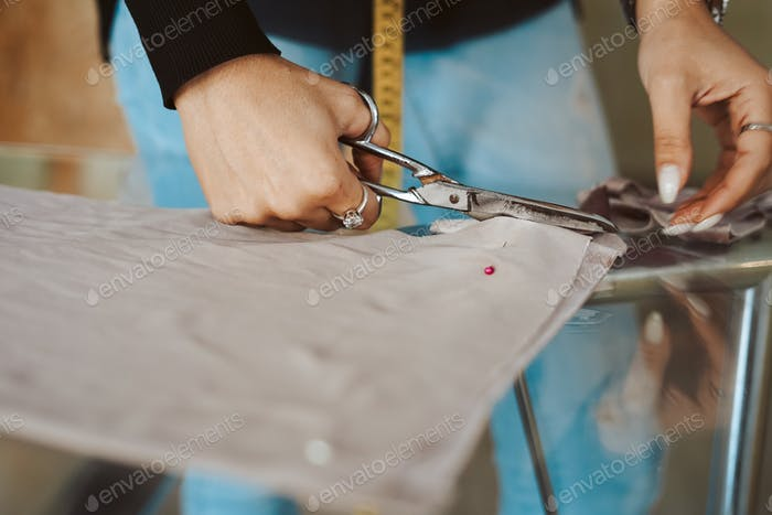 Tailor woman hands working on fabric