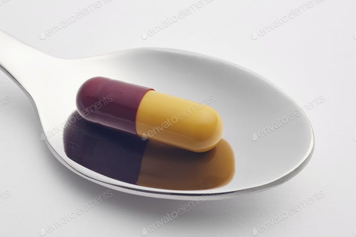 Pill and spoon over a white background. Medicament treatment. Healthcare