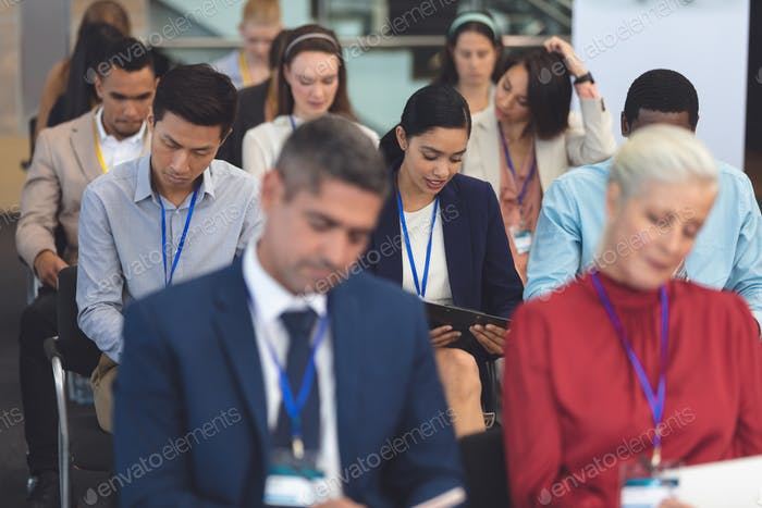 Young businesswoman reading document in a business seminar in office