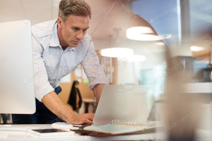 Businessman working on laptop while leaning at desk