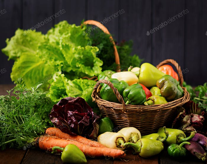Assortment of vegetables and green herbs. Market. Vegetables in a basket on a dark background