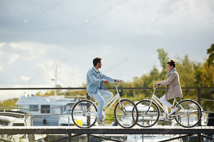 Beautiful couple on bicycles meeting on pier