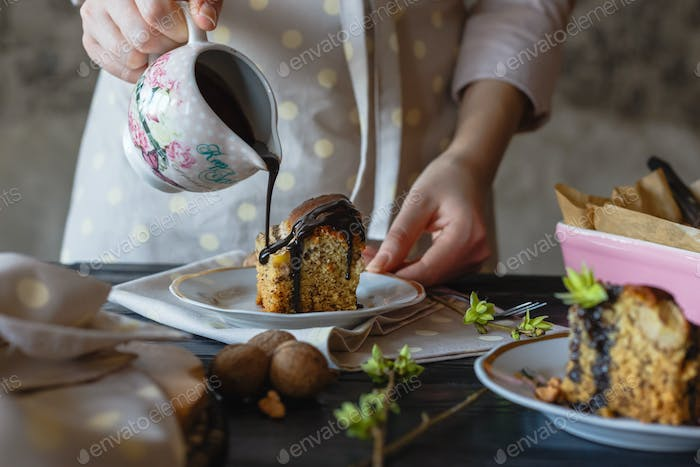 A baker girl pours hot chocolate on an incredibly appetizing piece of cake. Close-up view.
