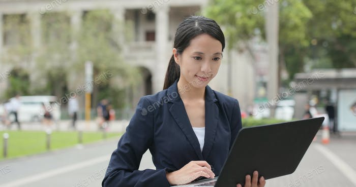 Businesswoman work on notebook computer in city of Hong Kong