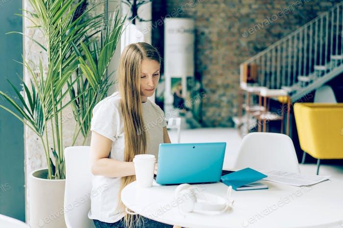 Junge Frau arbeitet an einem Laptop in einem Café an einem Tisch. Geschäftsfrau, Freiberuflerin, Remote-Arbeit.