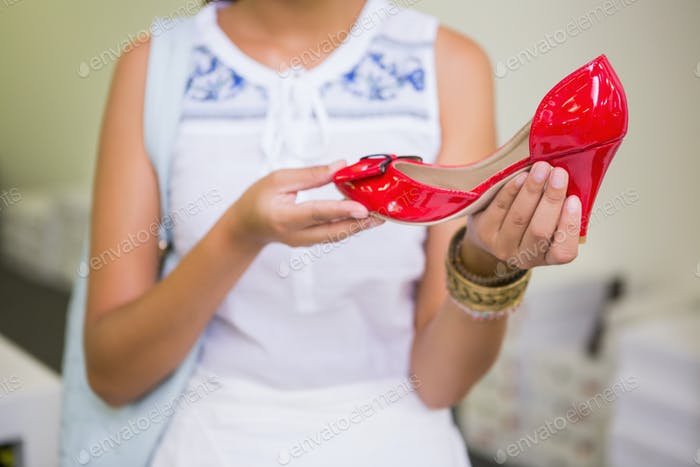 Young woman holding a shoe in the shoe store